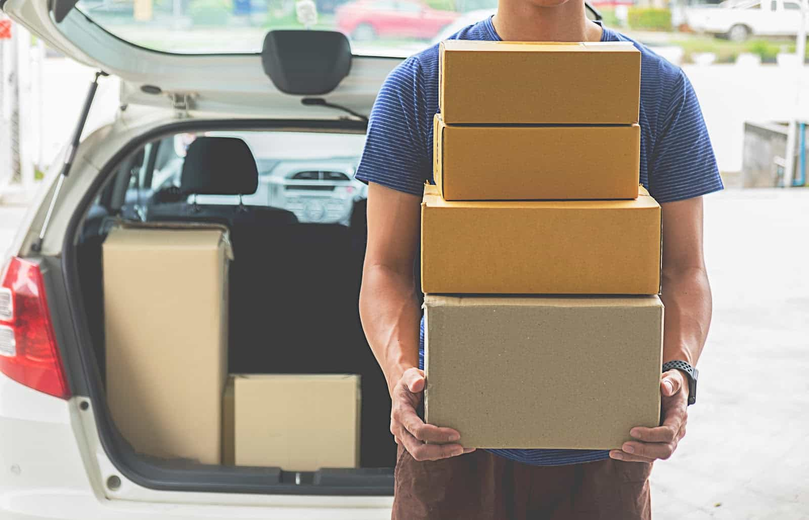 Apply for Amazon Flex: A delivery driver carrying boxes
