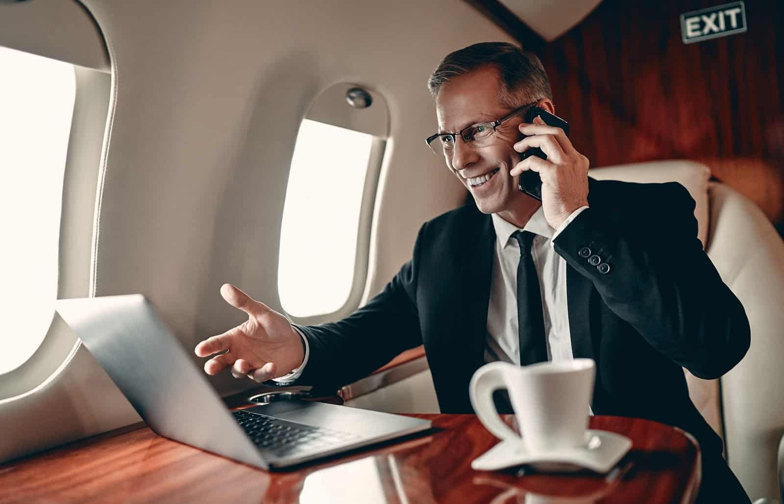 What is a chartered flight: A smiling business man gestures at his laptop on a private plane
